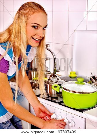 Portrait of happy woman cooking at kitchen.