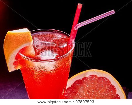 Top of red drink  with grapefruit and cube ice on dark background.