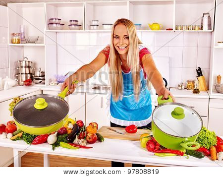 Happy woman cooking at kitchen. Hold two frying pan