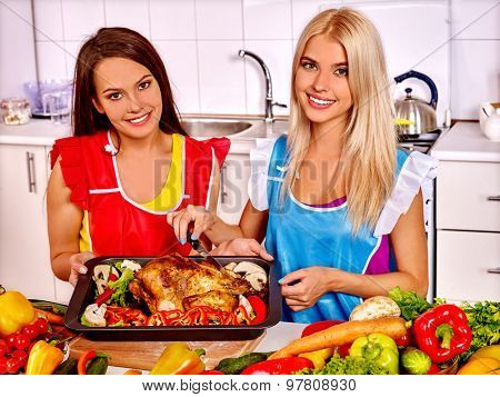 Happy young two pretty women cooking chicken at kitchen.
