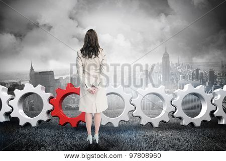 Rear view of businesswoman against cloudy sky over city