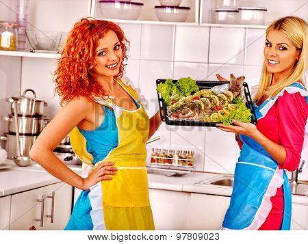 Happy women friend  prepare fish in oven.