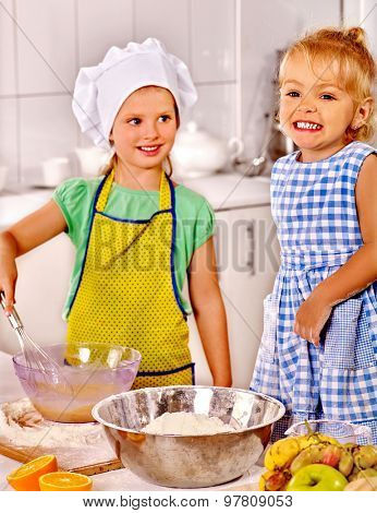 Children  with big metal bowl preparing  dough at kitchen.