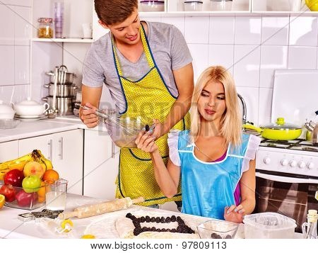 Young happy family of two people cooking at kitchen.