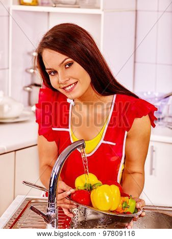 Happy woman washing fruit under water at kitchen.