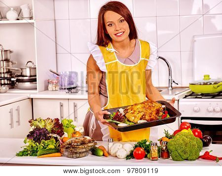 Happy young woman in yellow apron cooking chicken at home kitchen.