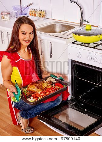Young woman with oven- tray cooking chicken at kitchen.