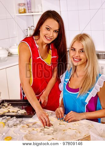 Two happy young woman  baking cookies in oven.