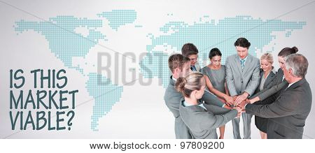 Smiling business team standing in circle hands together against green world map on white background