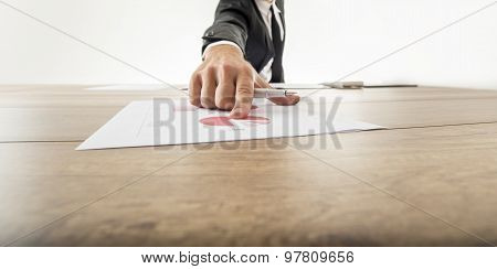 Businessman Pointing To A Graph On A Desk