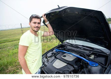 Man repairing a broken car by the road