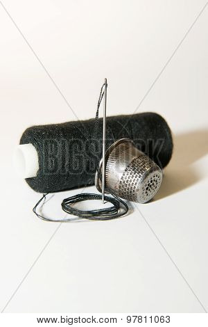 Needle And Thimble On A White Background