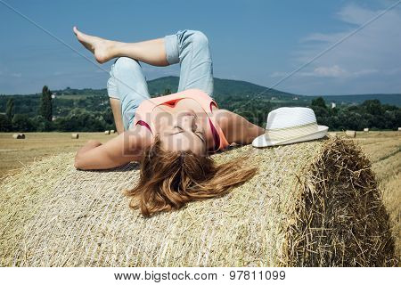 Young Woman Lying On A Stack Of Straw And Enjoying The Sunshine