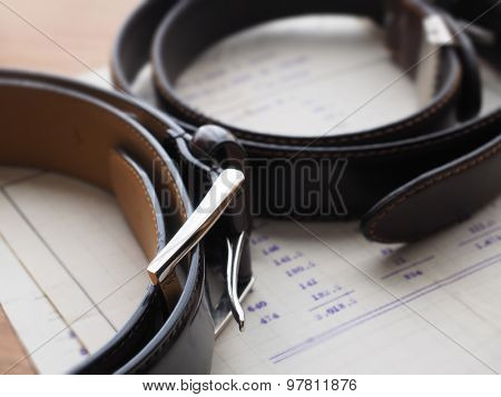 Two formal style leather belts on a hotel table or gentleman's desk.