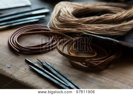 leather craft or leather goods making. work bench of a leather smith. Shallow depth of field.
