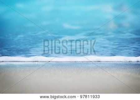 Leading edge of a gentle summer resort beach wave. Shallow depth of field.