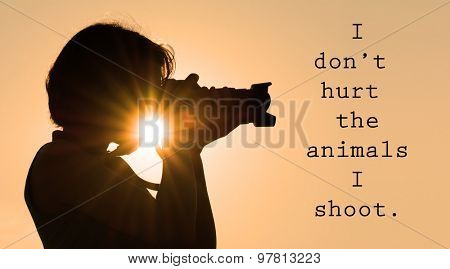 I don't hurt the animals I shoot - words with a silhouette with a young woman photographer aiming with her camera, with a sunburst