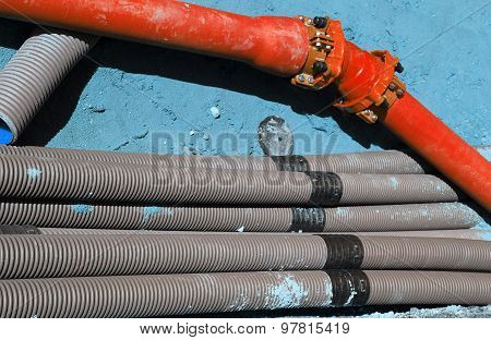 Corrugated Pipes And A Red Pipe In Digging In The Road Construction