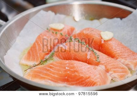 raw salmon with spices on pan
