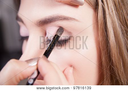 Stylist doing professional makeup of young woman. Close up