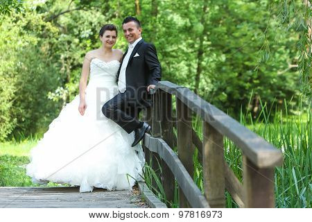 Newlyweds On Wooden Bridge