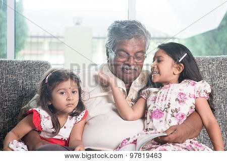 Grandparent and grandchildren reading story book together. Happy Indian family at home. Asian grandfather and granddaughters indoor lifestyle.