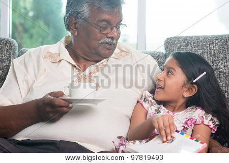 Grandparent and grandchild reading book together. Happy Indian family at home. Asian grandfather and granddaughter indoor lifestyle.