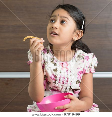Cute Indian girl eating traditional snack murukku. Asian child enjoying food, living lifestyle at home.