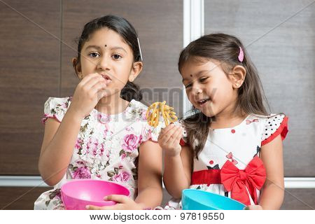 Two cute Indian girls eating food. Asian sibling or children enjoying traditional snack murukku, living lifestyle at home.