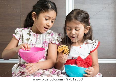 Two cute Indian girls eating traditional snack murukku. Asian sibling or children enjoying food, living lifestyle at home.