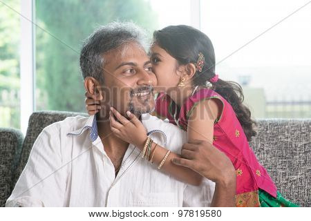 Indian daughter kissing father at home. Asian family indoors living lifestyle.