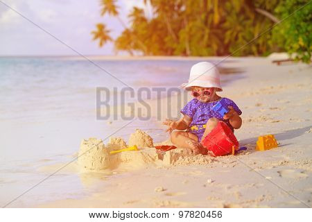 cute little girl building sandcastle on tropical beach
