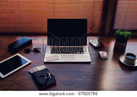 Freelancer needs workstation with open laptop computer and digital tablet with blank screen