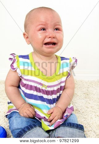 Ten month old baby girl crying with teething pain.