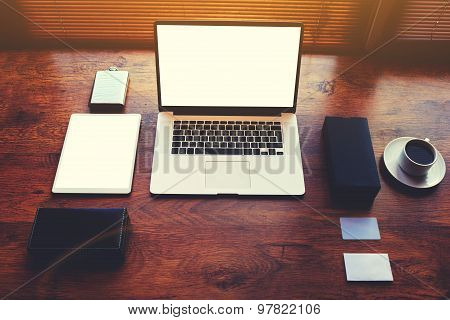 Workstation with cup of coffee and open laptop computer with blank copy space screen for text