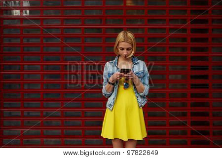 Female hipster student chatting on her smartphone against blank copy space bright background