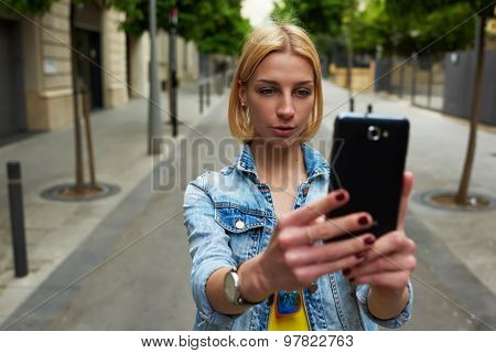 Stylish young woman photographing urban view with mobile phone camera during summer journey