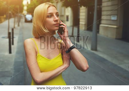 Successful young businesswoman talking on smart phone while standing at city street in summer