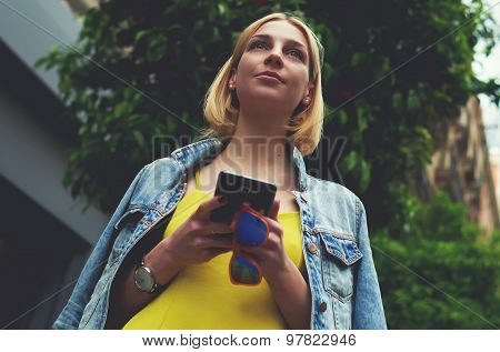 Low angle view with pretty young woman hold smartphone standing on mandarin tree background in city