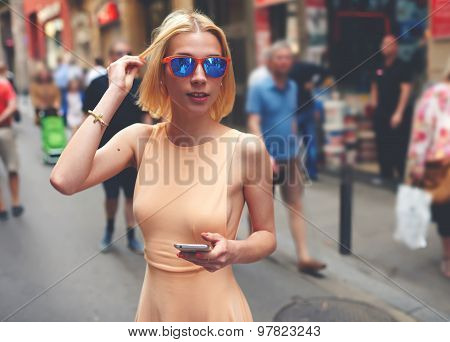 Pretty young female in summer dress and sunglases walking down street with smart phone