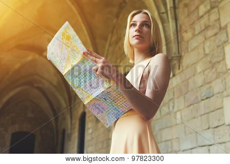 Portrait of young pretty female tourist reading a map while standing in antique town in summer