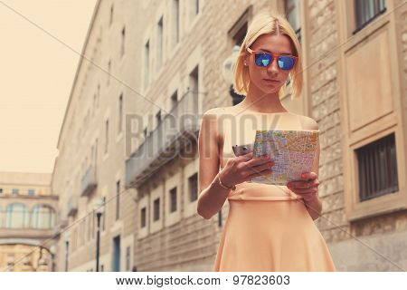 Stylish young female hipster studying a map while strolling in new city at summer vacation