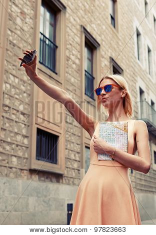 Gorgeous young woman making self portrait with a cell phone camera while enjoying a day