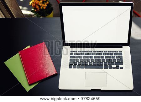 Top view of workplace with open laptop and colorful note book with blank copy space