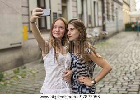 Selfie. Teenage girls take pictures of themselves on the smartphone on the street.