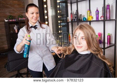 Hairstylist with hairspray and female client