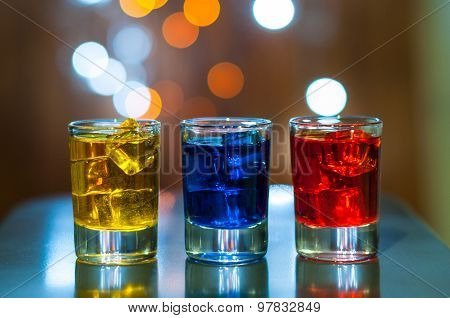 Various alcoholic cocktails on a bar counter with magic light bokeh background