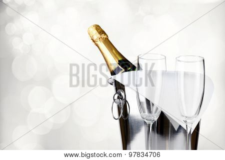 Bottle of champagne in pail and empty glasses on bright background