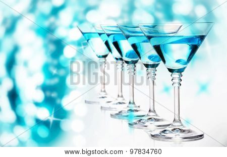 Blue cocktails in martini glasses on bright background
