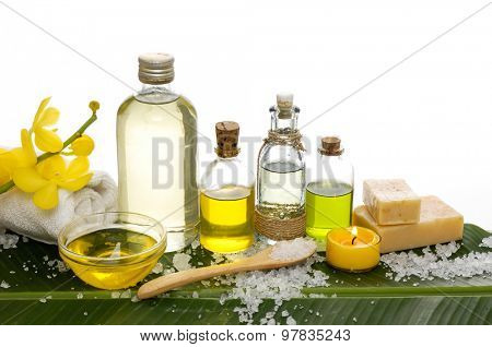 Spa set on banana leaf with bottle of oil, pile of salt